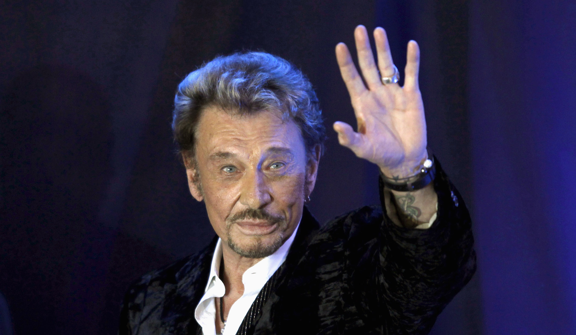 """French singer Johnny Hallyday waves to fans attending a ceremony to promote his new album """"Jamais seul"""" (Never alone) at the Virgin Megastore in Paris early March 28, 2011. REUTERS/Charles Platiau ( FRANCE - Tags: ENTERTAINMENT) - RTR2KHTG"""