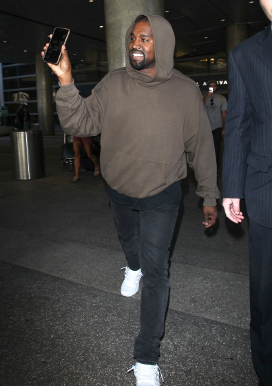 51894711 Kanye West arrives on a flight at LAX airport in Los Angeles, California on October 31, 2015. He can be seen smiling happily at his phone. FameFlynet, Inc - Beverly Hills, CA, USA - +1 (818) 307-4813